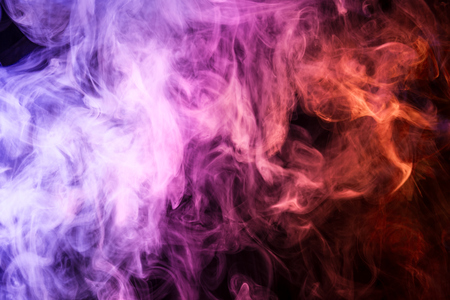 Thick colorful smoke of pink, and orange on a black isolated background. Background from the smoke of vape