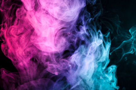 Thick colorful smoke of pink, red,  blue on a black isolated background. Background from the smoke of vape