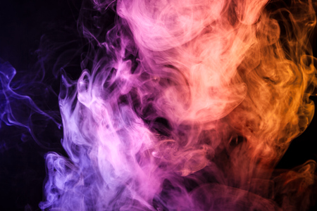 Thick colorful smoke of pink, orange,  blue on a black isolated background. Background from the smoke of vape  Stock Photo