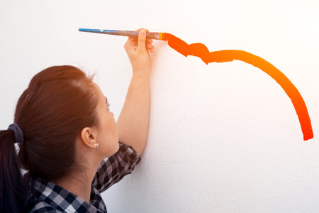 Close-up of a woman artist paints on a wall with a large wooden tassel in red