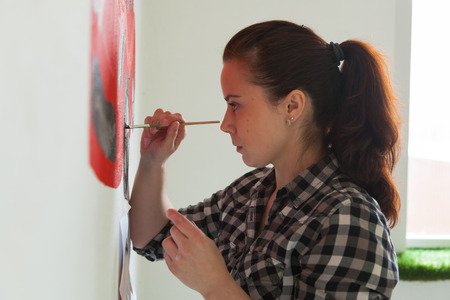 Young woman painter and mother boy draws for a child on a white wall a beautiful red car in a light children's room 免版税图像