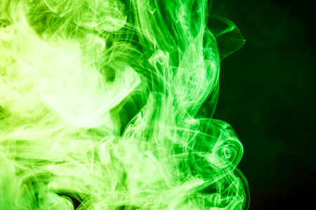 Cloud of green smoke on a black isolated background. Background from the smoke of vape  Stock Photo