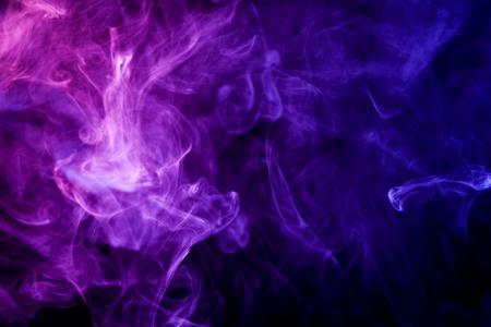 Dikke kleurrijke blauwe en roze rook op een geïsoleerde zwarte achtergrond. Achtergrond van de rook van damp Stockfoto