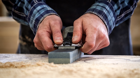 Close up of a experienced carpenter in work clothes and small buiness owner working in woodwork workshop, sharpening the tool with whetstone Standard-Bild