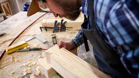 Carpenter in work clothes  doing woodwork in carpentry. small buiness owner work on wood plank in workshop Stock Photo