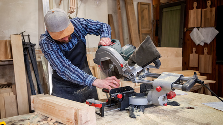Carpenter in work clothes and small buiness owner working in woodwork workshop, using a circular saw to cut through a wooden, on the table is a hammer and many tools Stock Photo