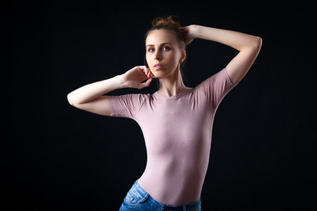 Studio shot for high fashion portrait of young elegant woman on beige top.