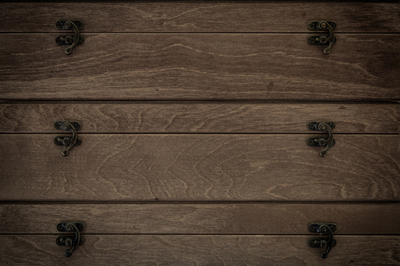 A close-up of a dark brown chest of drawers made from real wood with pine trees and metal arms