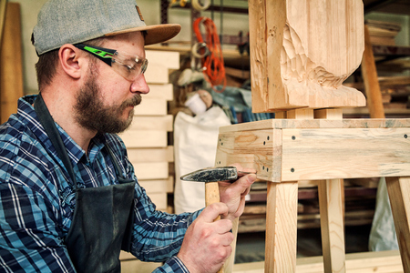 Experienced carpenter in work clothes and small buiness owner working in woodwork workshop, using a hammer hitting nails, on the table is a hammer and many tools