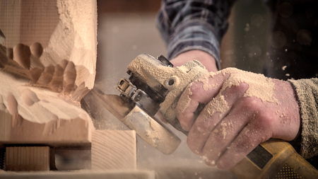Experienced carpenter in work clothes    saws a man's head with a tree , using an angle grinder  in the workshop, carpenter's hands in sawdust Banque d'images