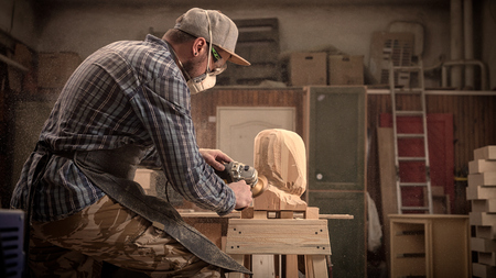 Ð¡arpenter,small buiness owner in work clothes saws a man's head with a tree , using an angle grinder in the workshop, around a lot of tools,wooden,furniture for work