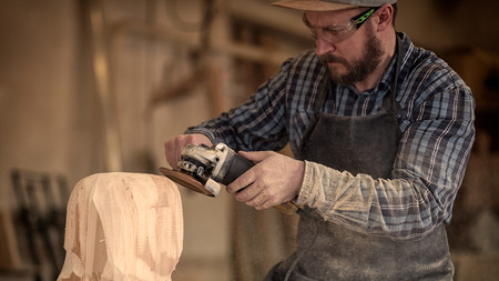 Ð¡arpenter, builder in work clothes saw to cut out sculpture from wooden a man's head, using an angle grinder in the workshop, around a lot of tools,wooden,furniture for work