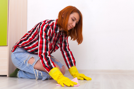 Сlose up of young woman  in jeans, yellow gloves and plaid shirt  washes the floor with a pink rag  in the childrens room with white walls and a green wardrobe. Womens housework and housekeeping concept Stock Photo