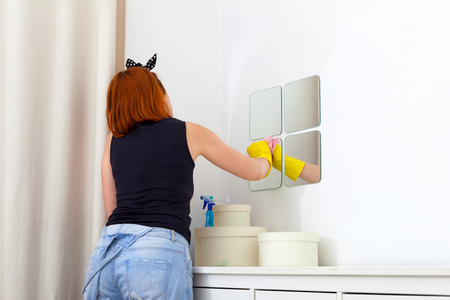 �¡lose up of young woman  in jeans, yellow gloves and plaid shirt   wipes a pink rag and white chest of drawers in the bedroom . Wet cleaning of the room from dust