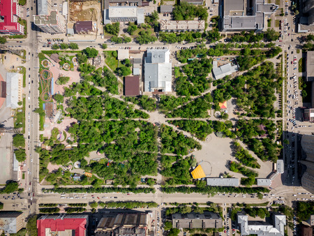 Aerial photography of a modern city park with green trees, attractions, high-rise buildings, roads with cars on a warm summer day. Helicopter drone shot Stock Photo