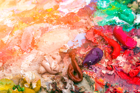 Close-up artist wins and paints with oil paints on the palette 写真素材