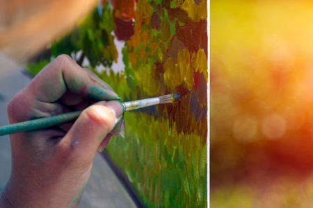 Close-up of a woman artist paints on canvas and an easel with oil paints in a city park on a sunny day Stock Photo - 103373777
