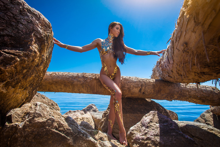 Beautiful blond attractive slender  woman model decorated with bodyart from a gold pattern from a film sensually posing on rocks near the sea on a warm summer day