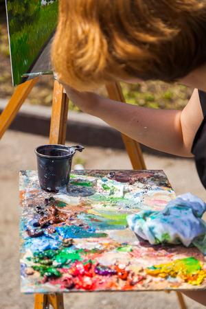 A close-up artist paints on a canvas an urban landscape of a summer embankment with atractions of oil paints Banco de Imagens