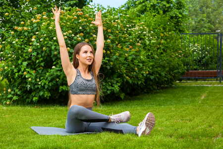 A dark-haired woman coach in a sporty short top and gym leggings does stretching the legs on the yoga mat, hands are raised upwards,  on a summer day in a park on a green lawn