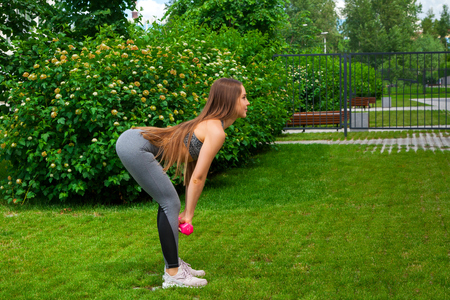A dark-haired woman coach in a sporty short top and gym leggings makes a deadlift with dumbbells on a summer day in a park on a green lawn