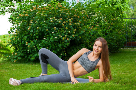A dark-haired woman coach in a sporty short top and gym leggings makes flips of his legs to the side, hands in front of him on a yoga mat on a green lawn in a park on a summer day Stock Photo