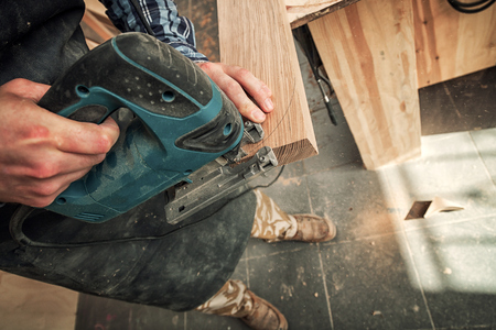 Close up of an experienced carpenter in work clothes and small buiness owner  is carving a wooden board on an  modern  hand drill in a light workshop side view, in the background a lot of tools
