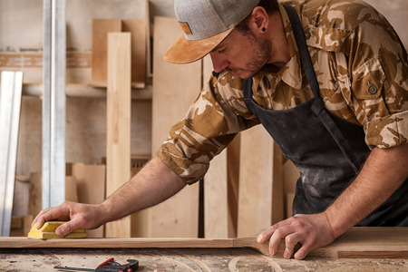 Experienced carpenter in work clothes and small buiness owner working in woodwork workshop,  using sandpaper for polishing childrens helicopter blades at worktable in workshop  on the table is a hammer and many tools