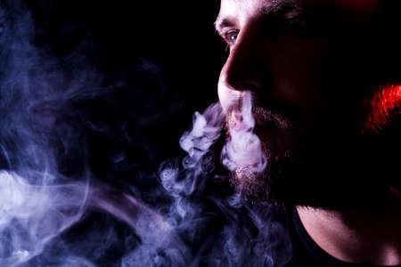 Un joven exhala una nube de humo de color rojo y azul sobre un negro aislado. Daño por fumar en el ejemplo de un joven atracador