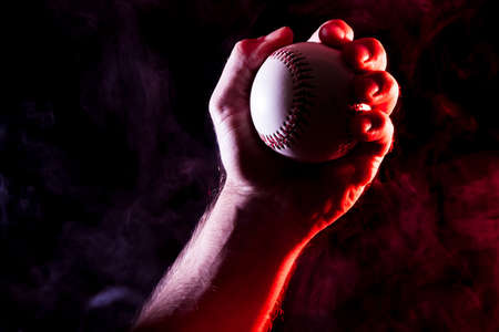 Close-up of a strong male hand holding a white baseball ball  against a background of colored  blue  and red smoke and black isolated background. Stock Photo