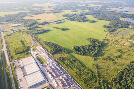 Top view of the industrial zone of the city, warehouses, green forest and a large field on a warm, sunny summer day