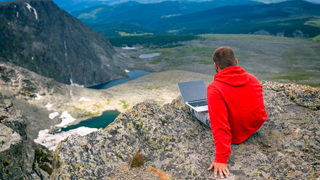 Young tourist man working on a laptop and sitting on the top of the mounting and looking at a beautiful  landscape.  Freelancer works outside the office. The concept of traveling and working outside the office