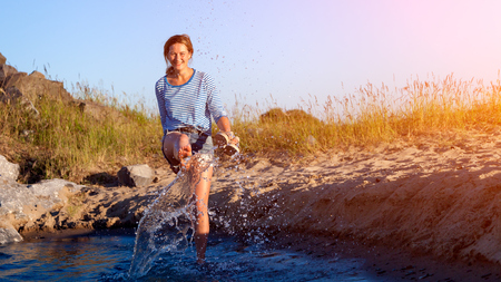 A cheerful dark-haired woman smiles, walks along the beach, kicks waves, sprays around a lot and enjoys the bright sun on a summer day. Concept of summer holidays at sea and live style 版權商用圖片