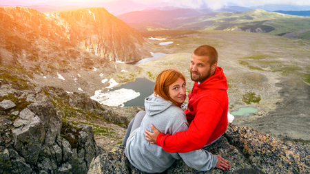 Atmospheric moment for lovers in the mountains.Hiking woman and man are sitting on the top of the mounting and looking at a beautiful landscape. Travel Lifestyle and survival concept rear view Banco de Imagens