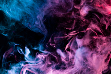 Cloud of pink,purple and blue smoke on a black isolated background. Background from the smoke of vape