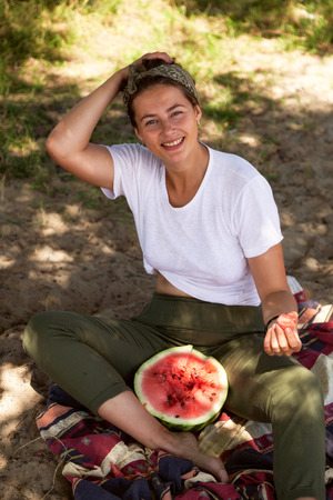 young beautiful woman laughs cheerfully, smiles, holds between the legs a big watermelon and eats, sitting on a sandy beach in a summer day near the sea