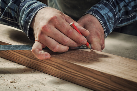 Close-up The man measures a wooden board with a ruler and marks with pencil the necessary points for slices