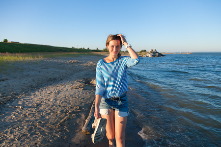A cheerful dark-haired woman smiles, walks along the beach, kicks waves, eat watermelon and enjoys the bright sun on a summer day. Concept of summer holidays at sea and live style