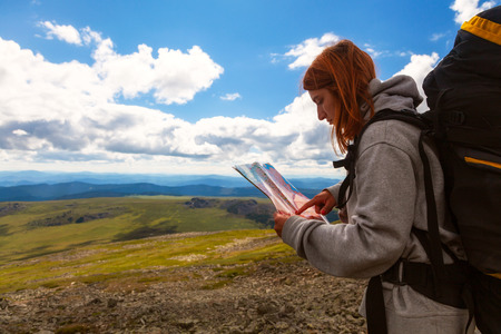 Stylish woman with backpack hiking, orient themselves to the terrain, study map and navigate the route through the mountains. Travel Lifestyle and survival concept rear view.