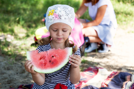 A portrait of a small cute little girl who eats a large piece of watermelon on a picnic on a summer warm day, in the background a beach and green grass Stock Photo