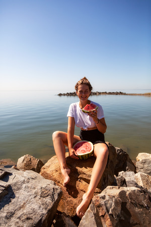 young beautiful woman laughing happily, smiling, holding between the legs a big watermelon and eating, sitting stone rocks on a summer day near the sea