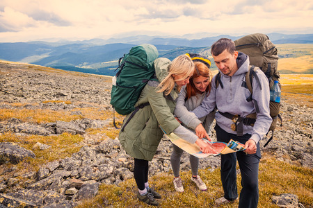 A team of travelers from two women and men with backpacks orient themselves to the terrain, study maps and navigate the route through the mountains. Travel Lifestyle and survival concept rear view. hipster traveler on top of mountains