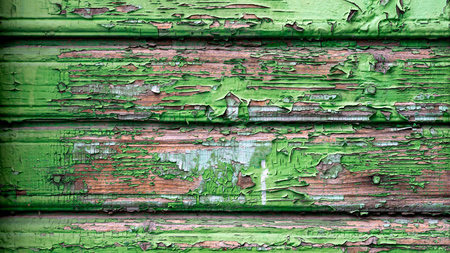 Close-up of an old wooden wall with peeling green paint. Close-up of a green wooden floor from the lining, wooden background Stock Photo