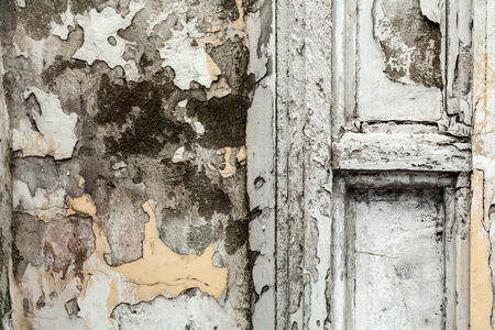 Close-up of an old peeling white gray wall with a door of an abandoned house