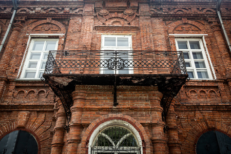 Close-up of a wooden metal  porch with a white old windows with an old house a mansion made of old brick Stock Photo