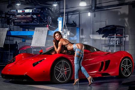 Novosibirsk, Rusland - 16 augustus 2018: Jonge vrouw fitness model in spijkerbroek en een zwembroek poseren voor reclame voor een sportwagen van een supercar Marussia in een autosalon