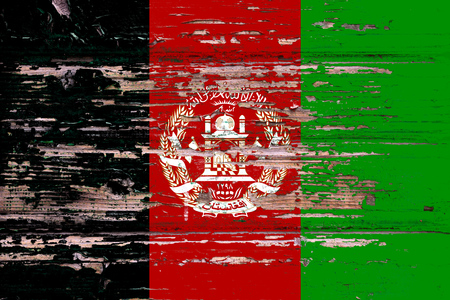 National flag of Afghanistan  on a dull wooden background