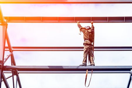 A man builder in a construction uniform without insurance moves around the construction of mettalical structures high above the ground. Violation of safety at the construction site