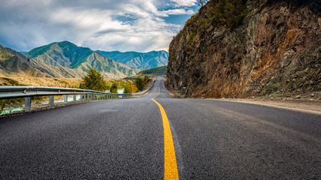 Asphalt road. Landscape with beautiful mountain road with a perfect asphalt. High rocks, amazing sky at sunset in summer. Panoramic. Travel background. Highway at mountains