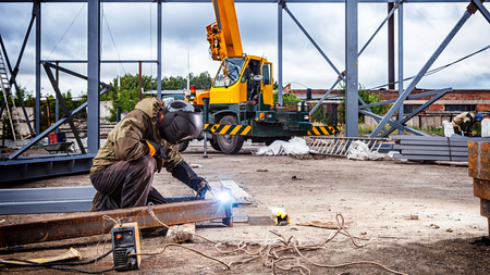 A strong man is a welder in brown uniform, welding mask and welders leathers, a metal product is welded with a arc welding machine at the construction site, blue sparks fly to the sides
